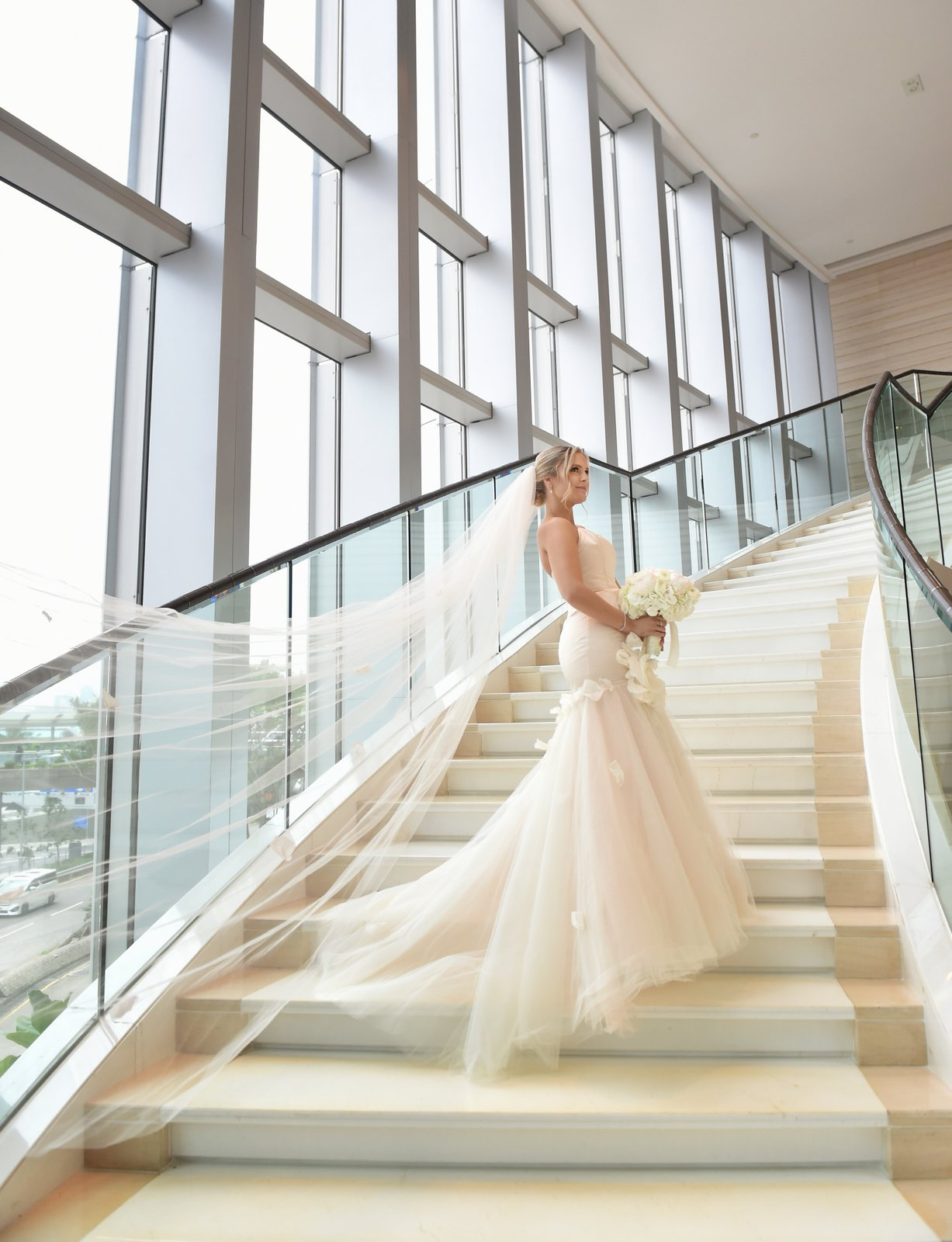Bride in long white dress on stair case