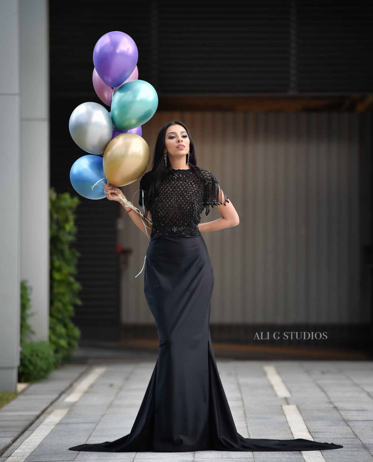 Editorial fashion shot of Payal Shah in a black dress holding balloons